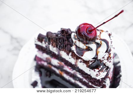 Closeup black forest chocolate cake with delicious on white marble table in coffee shop sweet and dessert concept selective focus