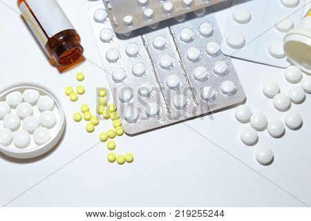 Various tablets - analgesics antidepressants vitamins antiviral drugs scattered on a white background.