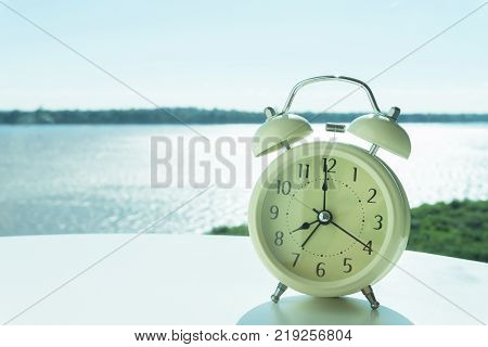 Alarm clock on white table with river and nature background morning relax time concept