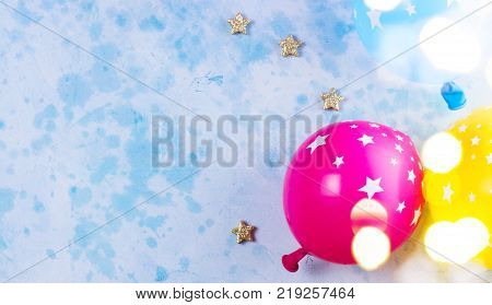 Bright colorful carnival or party scene of balloons on blue table. Flat lay style, birthday or party greeting card with copy space and bokeh lights