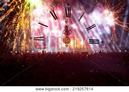 Colorful fireworks, clock close to midnight and crowd celebrating the New Year