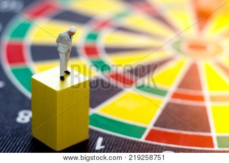 miniature business people standing on wooden box with dartboard. Thinking Target business concept.