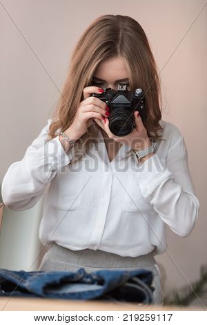 obscured view of self-employed businesswoman taking picture of products for customers at home office