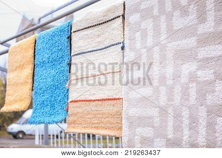 Different carpets hanging on rack outdoors