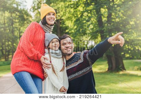 Three family members spend time together look at beautiful lake in park indicate with fingers being in good mood smile pleasantly. Father mother and daughter enjoy togetherness calm atmosphere