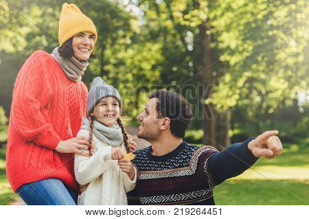 Lovely small girl with two pigtails wears knitted hat scarf and sweater holds leaf in hand looks joyfully into distance as her father shows her beautiful flower. Spending autumn days together