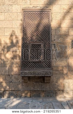 Ancient grunge wall with oriel window covered by interleaved wooden grid (Mashrabiya) Cairo Egypt
