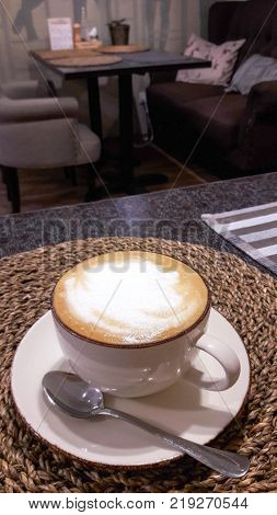 A cup of fresh cappuccino coffee in a cafe