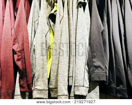 Modern clothes in a shop on a hanger. Shirts and sweaters of different colors and denim for youth. Clothes of different styles on the hanger in the showroom.