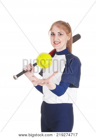 A smiling young woman standing in her blue softball uniform playing with the yellow ball holding her bat isolated for white background