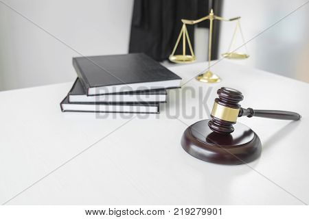 Attorney's suit Law book a gavel and scales of justice on a wooden white desktop Lawyer and justice concept law legal advice.