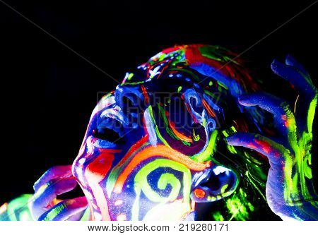 Close-up Portrait of an attractive young demonic girl in bright blacklight bodyart