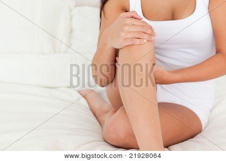 woman sitting crossleged on bed in bedroom