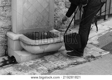 Man using community water to serve the dog. Old street washstand with man using water. water supply on the street.