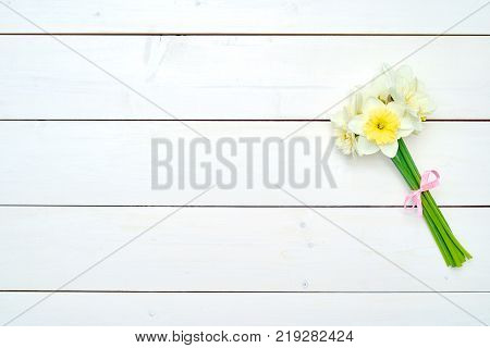 Bouquet of daffodil flowers on white wooden background copy space. Top view flat lay. White narcissus. Spring flowers. Greeting card for March 8 (Women's Day) Mother's day. Spring easter background