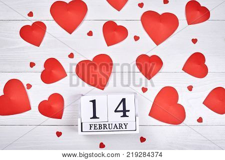 Valentines Day background with paper red hearts and wooden block calendar february 14 copy space. Greeting card mockup for Saint Valentines Day. Symbol of love. Love concept Top view flat lay