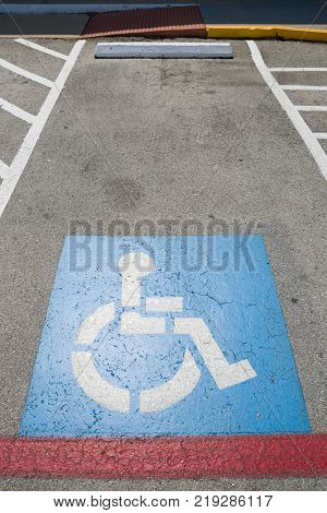 Top view on parking sign for disable people. Disabled parking space and wheelchair  symbols on asphalt.