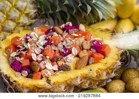 Fresh tropical fruit salad in pineapple with oat flakes raisins nuts sesame and mix sliced fruits ( dragon fruit pineapple banana mango papaya) - healthy breakfast. Thailand close up