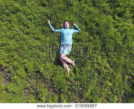 Beautiful Girl Lying Down Of Grass. The Girl Lies In A Turquoise Dress On The Lawn.
