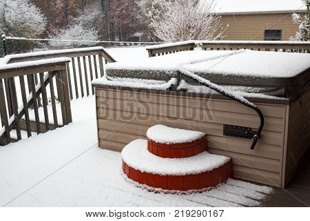 Covered hot tub on a residential porch in a snow storm horizontal aspect