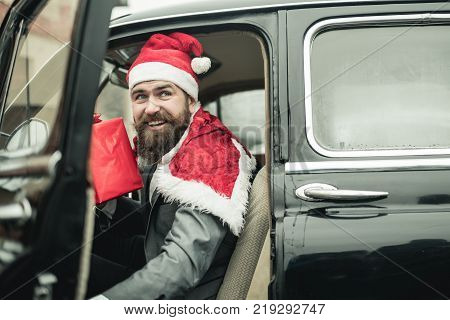 Man in red hat deliver xmas gifts in retro car. Santa Claus smile with present box. Merry christmas and happy new year. Winter holidays celebration. Boxing day concept.