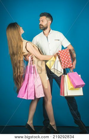 Black Friday happy holiday relations. Shopping and sale. Girl and bearded man hold present pack cyber Monday. Fashion shopaholic couple. Couple in love hold shopping bag near blue wall.