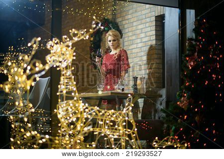 Festive fashion style decorations. Woman in red dress celebrate new year and christmas. Winter holidays celebration concept. Girl enjoy party food drinks in restaurant. xmas toast alcohol cheers.