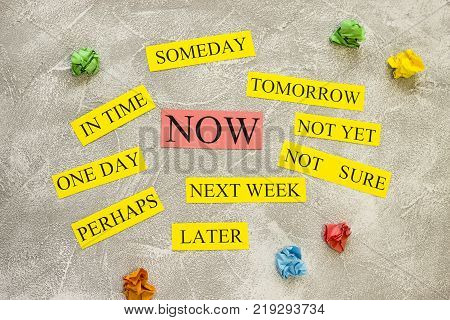Do not delay work till tomorrow. Motivation words on a light concrete background, NOW inscription in the middle. Space for your text or product display.
