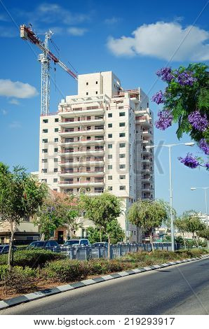 Rishon LeZion, Israel-June 10, 2017: Amazing view of 15-story residential building is almost constructed. Tower crane still works. There are urban road and blooming purple jacaranda tree on the foreground.