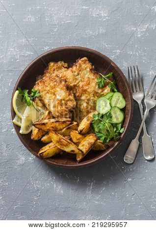 Fried fish and garlic baked potatoes on a grey background top view. Fish and chips. Appetizers or snacks