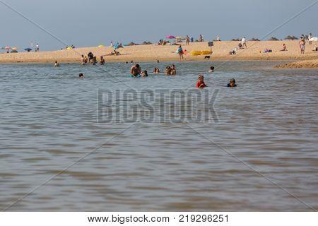 PRAIA DA BORDEIRA, PORTUGAL - AUGUST 20, 2017: People at the beach of the famous Praia da Bordeira. This beach is a part of famous tourist region of Algarve.