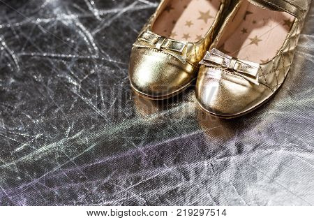 Golden ballet shoes on silver background, close up photo