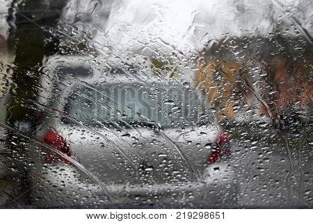 Look through car glass. On the street it is raining