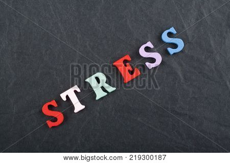 STRESS word on black board background composed from colorful abc alphabet block wooden letters, copy space for ad text. Learning english concept