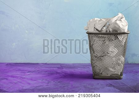 A trash can for paper. Beautiful unusual background with place for text. A full trash can for crumpled paper sheets.