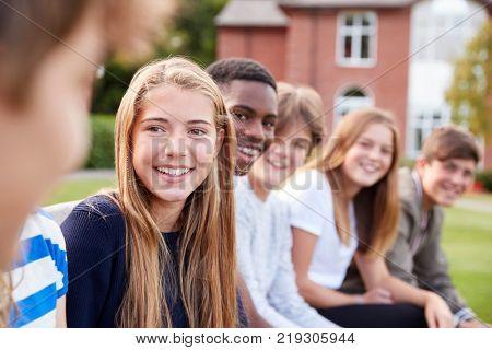 Group Of Teenage Students Sitting Outside School Buildings