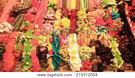 Colorful sweets at La Boqueria market in Barcelona, Spain. Large assortment of different gummy candies.