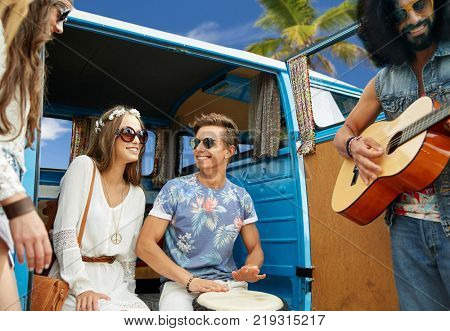 summer holidays, road trip, travel and people concept - happy young hippie friends having fun and playing music over minivan car over beach background