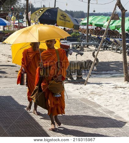 Sihanoukville Cambodia - April 30 2014: young monks with umbrellas walking under the sun along the town beach
