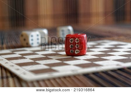 Stack of three white plastic dices and one red dice on brown wooden board background. Six sides cube with black dots. Number 6