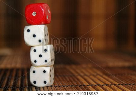 Stack of three white plastic dices and one red dice on brown wooden board background. Six sides cube with black dots. Number 1 3 4 5