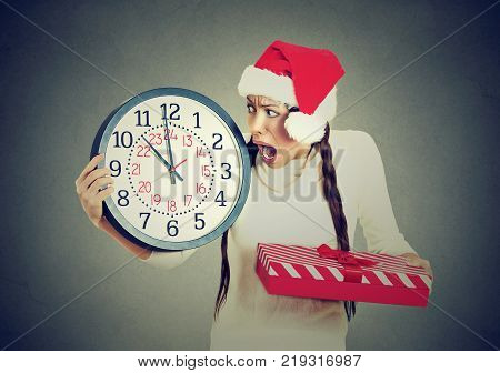 Closeup portrait worried stressed in a hurry young woman wearing red santa claus hat holding clock gift box isolated gray background. Emotion funny face expression last minute christmas shopping