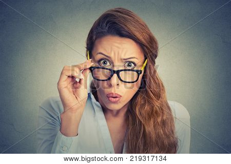 Surprised frustrated young woman taking of glasses
