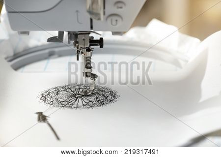 embroidery with embroidery machine - dandilon on white leatherette - view on embroidery process and machine head in bright sunny light mood