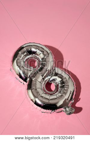 a silvery balloon in the shape of the number 8 against a pink background, with a blank space on top