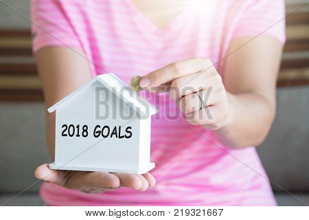 2018 goals with women hand putting money coin in piggy bank Saving money concept concept of financial savings to buy a house Growth business money.
