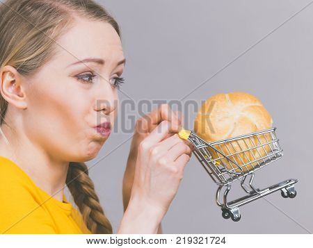 Buying gluten food products concept. Skeptical woman holding shopping cart trolley with bun breal roll having bizarre face expression.