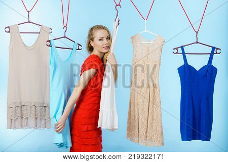 Young blonde long hair woman in clothes shop store picking summer outfit dresses hanging on clothing hangers on blue. Sale shopping concept