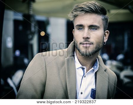 Handsome trendy blond man standing outdoor in European city setting with elegant old historic building behind