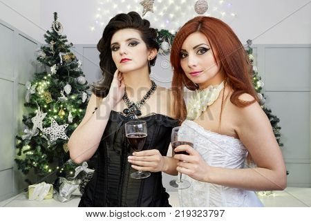 Collage with red-haired woman in white dress and dark-haired woman in black dress stand with glasses of wine in christmas room